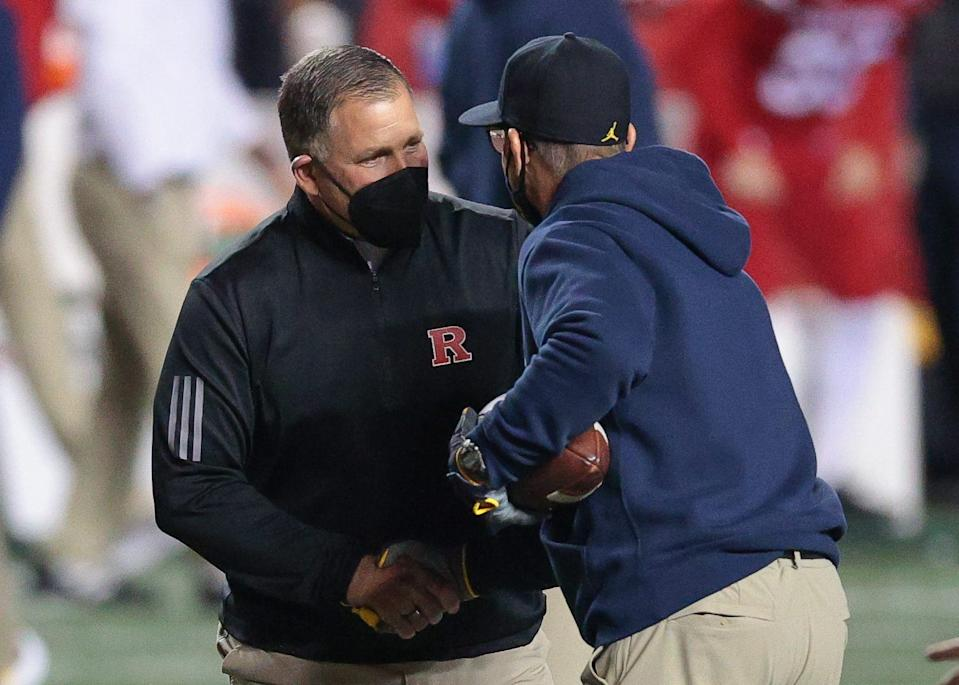 Rutgers Scarlet Knights football coach Greg Schiano, left, shakes hands with Michigan Wolverines coach Jim Harbaugh before their game at SHI Stadium on Saturday, Nov. 21, 2020.