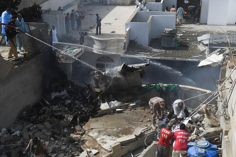 Police spray water on the part of a Pakistan International Airlines aircraft after it crashed at a residential area in Karachi on May 22, 2020. - A Pakistan passenger plane with more than 100 people believed to be on board crashed in the southern city of Karachi on May 22, the country's aviation authority said. (Photo by Asif HASSAN / AFP) (Photo by ASIF HASSAN/AFP via Getty Images)