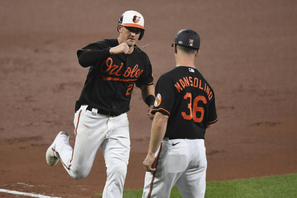 Baltimore Orioles' Austin Hays is greeted by third base coach Tony Mansolino after a solo home run off Miami Marlins starting pitcher Sandy Alcantara during the fourth inning of a baseball game Tuesday, July 27, 2021, in Baltimore. (AP Photo/Terrance Williams)