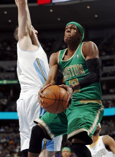 Boston Celtics guard Rajon Rondo, front, goes up for a shot past Denver Nuggets center Timofey Mozgov, of Russia, in the first quarter of an NBA basketball game in Denver on Saturday, March 17, 2012. (AP Photo/David Zalubowski)