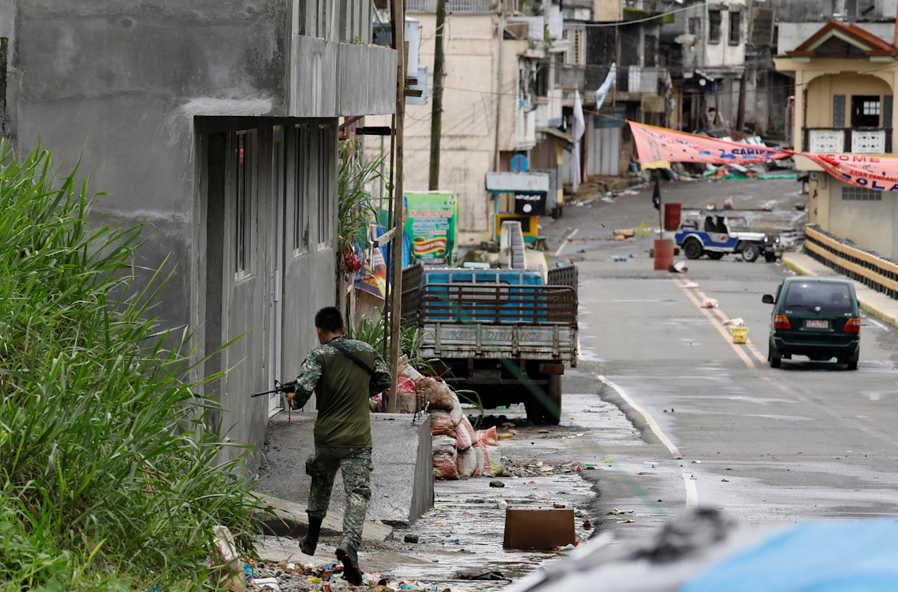 A government soldier is pictured running and overlooking the Maute group stronghold in Marawi City in southern Philippines May 29, 2017. REUTERS/Erik De Castro