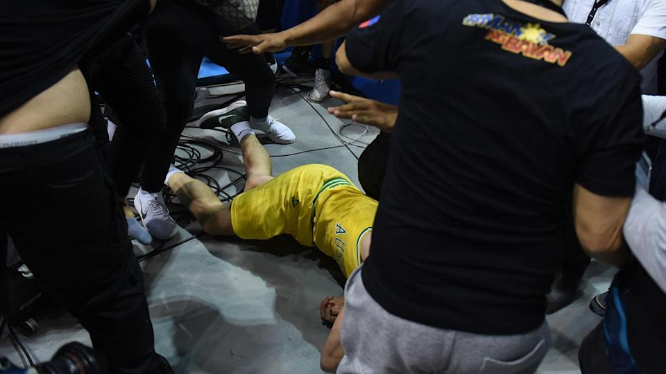 Goulding lays on the floor as players from benches run to their teammates who figured in a brawl during the match between Australia and the Philippines for the FIBA Asian Qualifiers held at the Philippine Arena in the province of Bulacan, north of Manila in 02 July 2018. Australia beat the Philippines by default following a brawl in the third quarter that shocked basketball fans all over the world. (Photo by George Calvelo/NurPhoto via Getty Images)