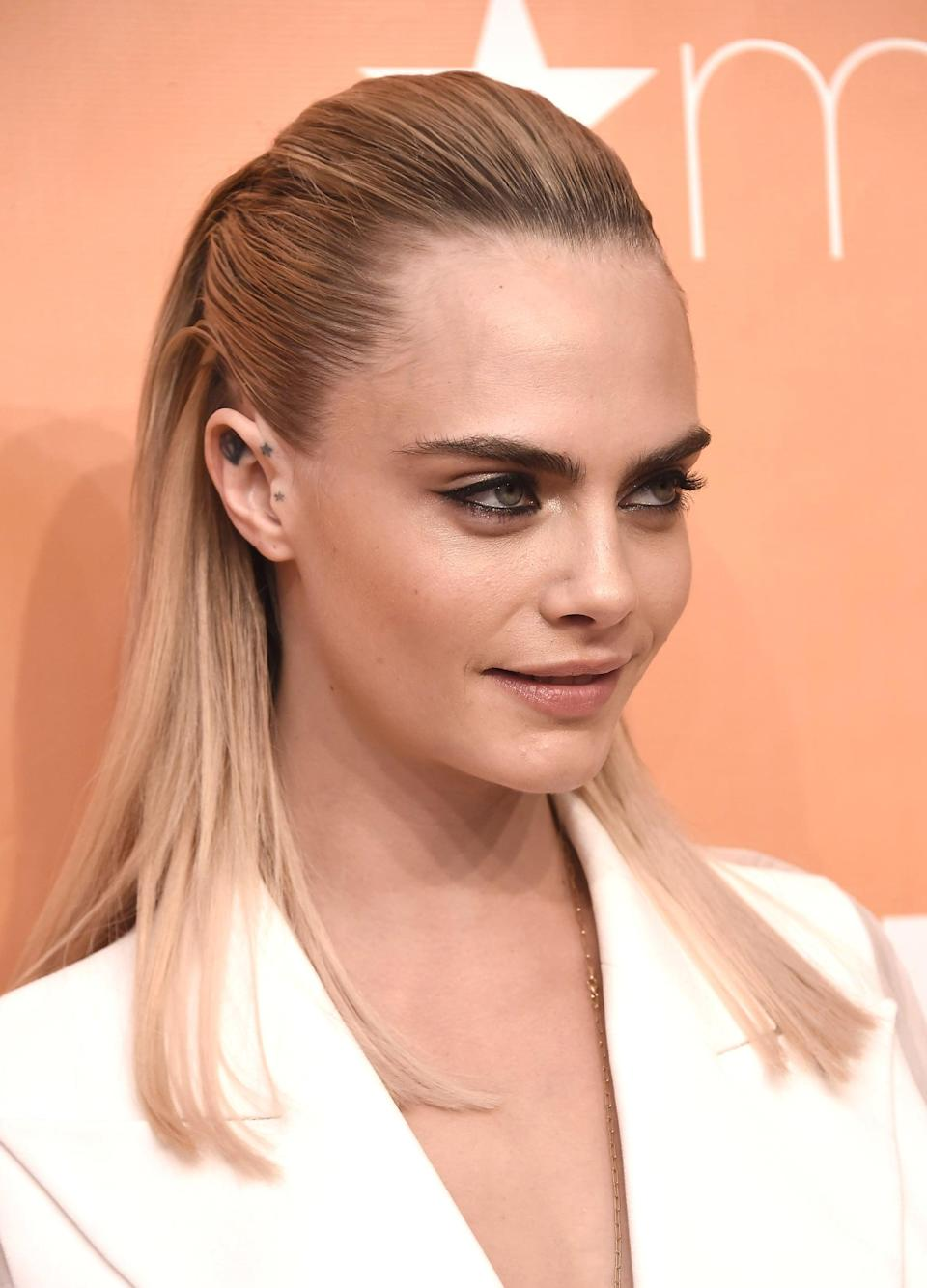 <p>Delevingne defies gravity with this slicked back, half-up style that doesn't seem to include a single hair tie.</p>