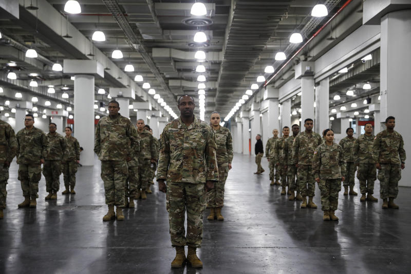 """The National Guard stands in formation at the Jacob Javits Center, Monday, March 23, 2020, in New York. New York City hospitals are just 10 days from running out of """"really basic supplies,"""" Mayor Bill de Blasio said late Sunday. De Blasio has called upon the federal government to boost the city's quickly dwindling supply of protective equipment. The city also faces a dearth of ventilators to treat those infected by the coronavirus. (AP Photo/John Minchillo)"""