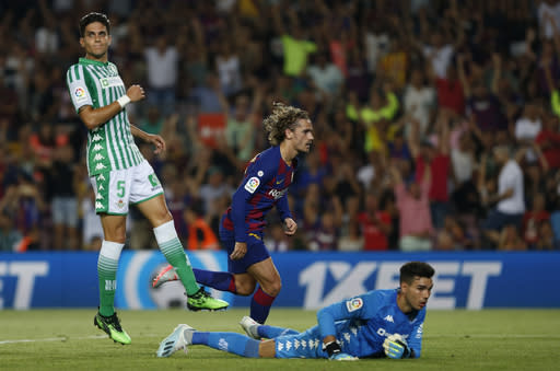 Barcelona's Antoine Griezmann, center, scores his side's first goal during the Spanish La Liga soccer match between FC Barcelona and Betis at the Camp Nou stadium in Barcelona, Spain, Sunday, Aug. 25, 2019. (AP Photo/Joan Monfort)
