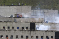Tear gas rises from parts of Turi jail where an inmate riot broke out in Cuenca, Ecuador, Tuesday, Feb. 23, 2021. Deadly riots broke out in prisons in three cities across the country due to fights between rival gangs, according to police. (AP Photo/Marcelo Suquilanda)