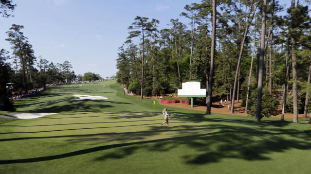 An unidentified patron runs across the 10th green during the third round of the Masters golf tournament Saturday, April 12, 2014, in Augusta, Ga. (AP Photo/David J. Phillip)