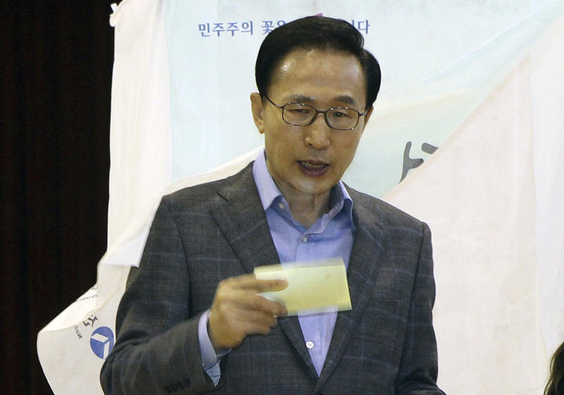 South Korean Presidential Lee Myung-bak exits a booth after writing down a candidate to cast his ballot in the parliamentary elections at a polling station in Seoul, South Korea, on Wednesday, April 11, 2012. (AP Photo/Kim Byung-man) KOREA OUT