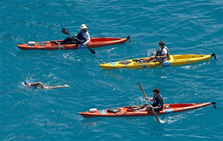 Diana Nyad, positioned about than two miles off Key West, Florida in this September 2, 2013 handout photo, is escorted by kayakers as she swims towards the completion of her 111-mile trek from Cuba to the Florida Keys. REUTERS/Andy Newman/Florida Keys News Bureau/Handout