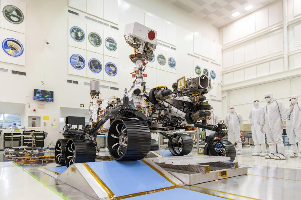"""FILE - In this Dec. 17, 2019 photo made available by NASA, engineers watch the first driving test for the Mars 2020 rover, later named """"Perseverance,"""" in a clean room at the Jet Propulsion Laboratory in Pasadena, Calif. (J. Krohn/NASA via AP)"""