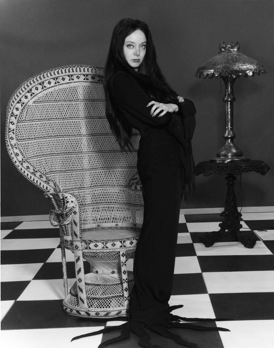 """<p>""""Darling, I always wear black,"""" Morticia Addams purred. And what more recognizable LBD costume than this? It also works well for a group costume—or maybe Wednesday Addams for a gothic twist on Mommy and me costumes? </p>"""