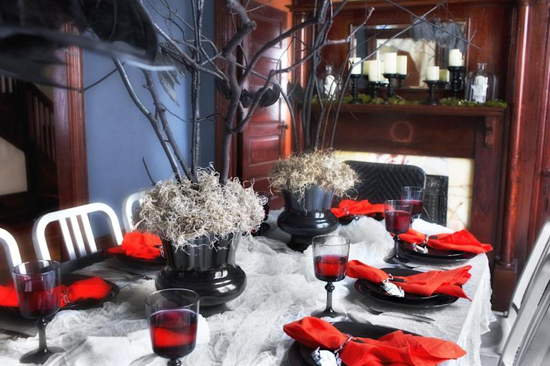 This undated photo provided by Brian Patrick Flynn shows bare branches, spray-painted black and secured in vases with gravel, floral foam and a layer of moss, that make a stunning and inexpensive Halloween centerpiece created by designer, Brian Patrick Flynn for HGTV.com, in Atlanta. (AP Photo/Brian Patrick Flynn/HGTV.com, Scripps Networks Interactive/Sarah Dorio)