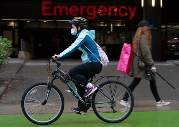 A woman cycles past the emergency entrance of Vancouver General Hospital in April. (Jonathan Hayward/Canadian Press - image credit)
