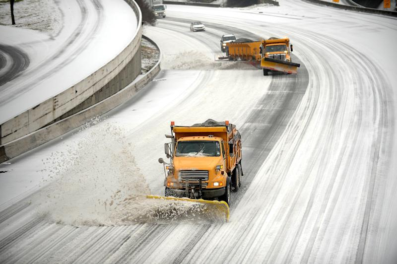 """Snow plows clear downtown lanes on Interstate 75/85 during a winter storm on Wednesday, Feb. 12, 2014, in Atlanta. Across the South, winter-weary residents woke up Wednesday to a region encased in ice, snow and freezing rain, with forecasters warning that the worst of the potentially """"catastrophic"""" storm is yet to come. (AP Photo/David Tulis)"""