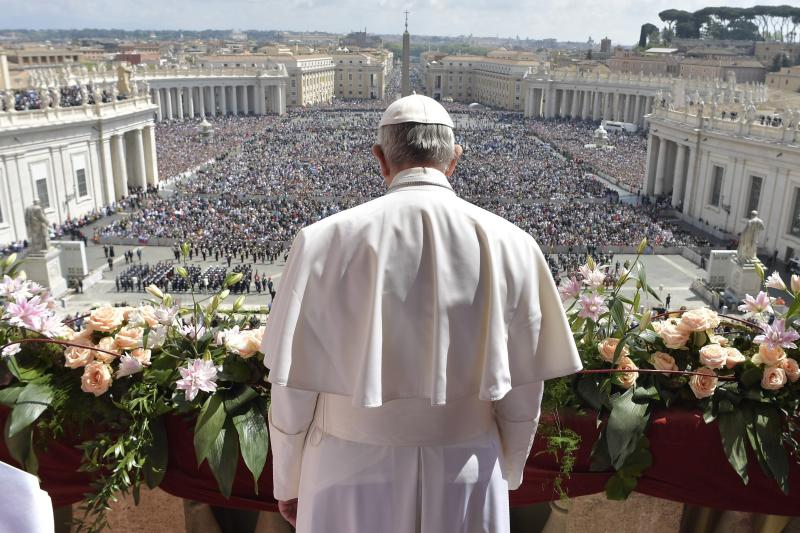 """Pope Francis addresses the crowd prior to delivering his Urbi et Orbi (to the city and to the world) message from the main balcony of St. Peter's Basilica, at the Vatican, Sunday, April 16, 2017. On Christianity's most joyful day, Pope Francis lamented the horrors generated by war and hatred, delivering an Easter Sunday message that also decried the """"latest vile"""" attack on civilians in Syria. (L'Osservatore Romano/Pool Photo via AP)"""