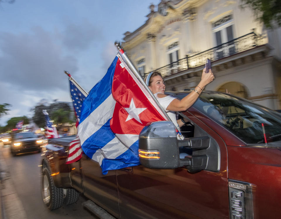 Members of the 'Gran Caravana,' (Big Caravan), pass the Cuba-centric San Carlos Institute on Duval Street Wednesday, July 14, 2021, in Key West, Fla., rallying support for the Cuban people. Roughly four dozen vehicles started the permitted parade 100 miles north in Key Largo, with more vehicles joining along U.S. 1, and ultimately connceting with dozens more in Key West for a parade on the island's main drag, Duval Street. (Rob O'Neal/The Key West Citizen via AP)