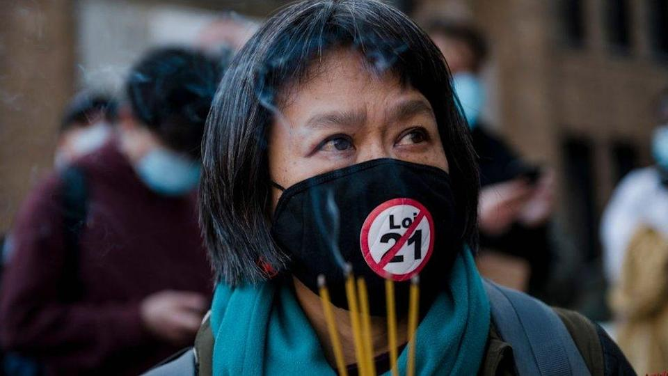 May Chiu lights incense during a vigil following a demonstration against anti-Asian racism in Montreal, Quebec, Canada, on March 21, 2021.