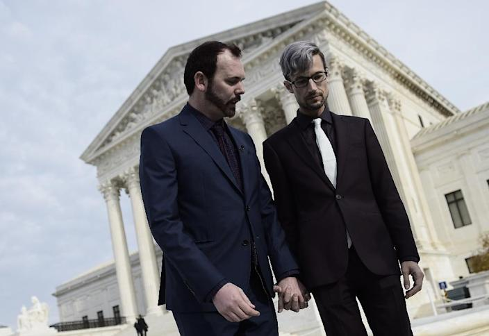 Charlie Craig (L) and Dave Mullins hold hands outside the US Supreme Court (AFP Photo/Brendan SMIALOWSKI)