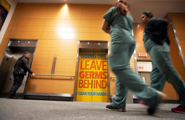 Staff and visitors walk past a sign indicating to wash hands on the elevator doors at the Jewish General Hospital in Montreal, Quebec, Canada March 2, 2020. REUTERS/Christinne Muschi