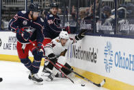 Chicago Blackhawks' Pius Suter, right, tries to clear the puck away from Columbus Blue Jackets' Mikhail Grigorenko, left, and Jack Roslovic during the second period of an NHL hockey game Saturday, April 10, 2021, in Columbus, Ohio. (AP Photo/Jay LaPrete)