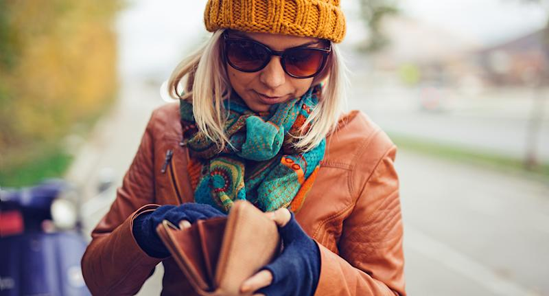 A woman looking through her wallet. NSW drivers will be able to ditch their plastic licences if they want to from August.
