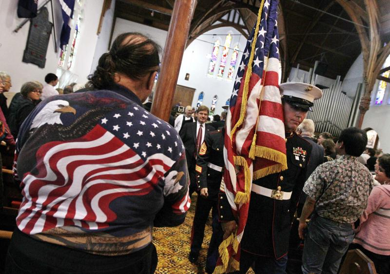 A member of the U.S. Marines carries their national flag past a man wearing a stars and stripes shirt during a special service to commemorate the 10th anniversary of the Sept. 11 terrorist attacks, at a church in New Plymouth, New Zealand, Sunday, Sept. 11, 2011. The US team will play Ireland in their opening Rugby World Cup game later today.  (AP Photo/Dita Alangkara)