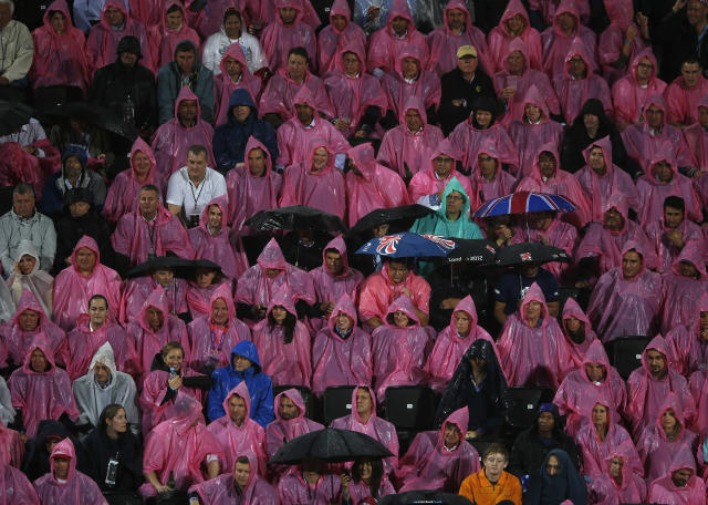 Spectators shelter from the rain as they watch the women's beach volleyball semifinal match between April Ross and Jennifer Kessy of the U.S. and Brazil's Juliana and Larissa at Horse Guards Parade during the London 2012 Olympic Games August 7, 2012. REUTERS/Marcelo Del Pozo (BRITAIN - Tags: OLYMPICS SPORT VOLLEYBALL TPX IMAGES OF THE DAY)