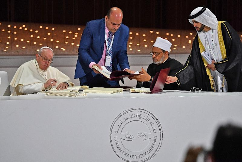 Pope Francis (L) and the Grand Imam of Cairo-based Al-Azhar Sheikh Ahmed al-Tayeb (2nd-R) sign documents during the Human Fraternity Meeting at the Founders Memorial in Abu Dhabi on February 4, 2019 (AFP Photo/Vincenzo PINTO                      )