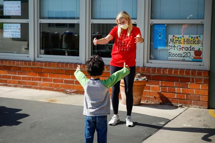 "Observing physical distance, first-grade teacher Caitlin Hicks gives an air hug to Sid Solomon, 6, as she meets students one final time in June, when students pick up schoolwork left behind after Center Street Elementary in El Segundo closed in March. <span class=""copyright"">(Jay L. Clendenin / Los Angeles Times)</span>"