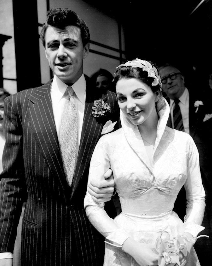 <p>In her first of five marriages, British actress Joan Collins married Maxwell Reed at Caxton Hall in London. The ceremony included friends and family and the bride wore a high collared brocade satin wedding gown. </p>