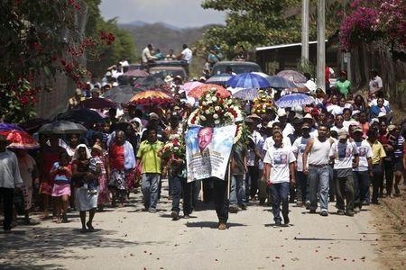 A man carries a wreath and a banner as relatives and friends of Antonio Zambrano-Montes carry his coffin toward the cemetery in Pomaro, in the Mexican state of Michoacan March 7, 2015. REUTERS/Alan Ortega