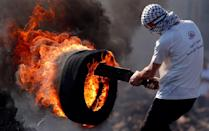 <p>A Palestinian protester carries a burning tire during clashes with Israeli forces following a weekly demonstration against the expropriation of Palestinian land by Israel in the village of Kfar Qaddum, near Nablus in the occupied West Bank. (Jaafar Ashtiyeh/AFP/Getty Images) </p>