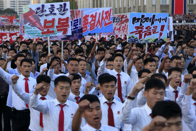 """DELETES NUMBER OF PEOPLE - North Koreans gather at Kim Il Sung Square to attend a mass rally against America on Saturday, Sept. 23, 2017, in Pyongyang, North Korea, a day after the country's leader issued a rare statement attacking Donald Trump. The sign on the left reads """"decisive revenge"""" and the sign on the right reads """"death to the American imperialists."""" (AP Photo/Jon Chol Jin)"""
