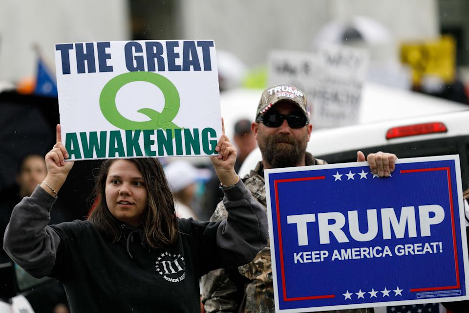 Demonstrators hold signs promoting the QAnon conspiracy theory and President Donald Trump while protesting coronavirus restrictions at the State Capitol in Salem, Ore. on May 2, 2020. (John Rudoff/Anadolu Agency via Getty Images)
