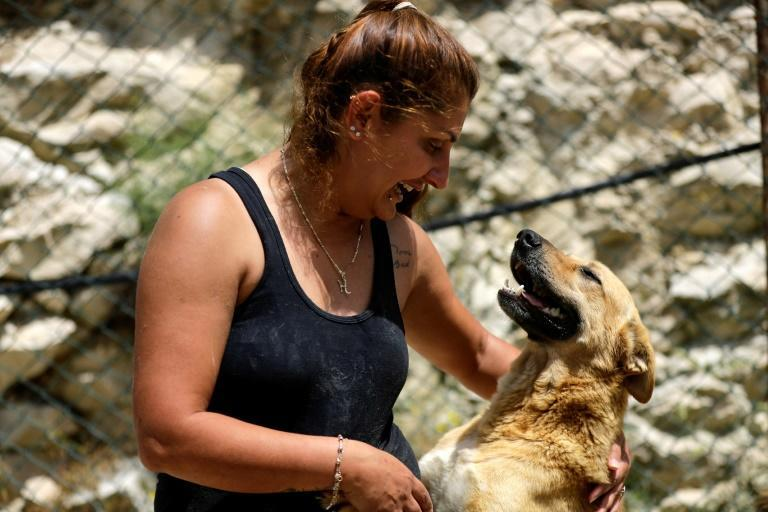 Volunteer Ghada al-Khateeb plays with a rescued dog at Woof N' Wags shelter on the outskirts of the village of Kfar Chellal south of Beirut