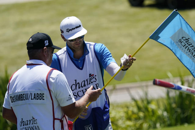 Dustin Johnson's caddie Austin Johnson, right, wipes down a putting green flag pole with a disinfectant wipe along with Bryson DeChambeau's caddie Tim Tucker during the first round of the Charles Schwab Challenge golf tournament at the Colonial Country Club in Fort Worth, Texas, Thursday, June 11, 2020. (AP Photo/David J. Phillip)