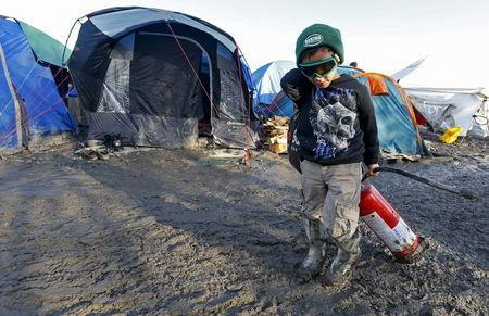 A young migrant pulls a fire extinguisher in a muddy field at a camp of makeshift shelters for migrants and asylum-seekers from Iraq, Kurdistan, Iran and Syria, called the Grande Synthe jungle, near Dunkirk, France, January 25, 2016. REUTERS/Yves Herman