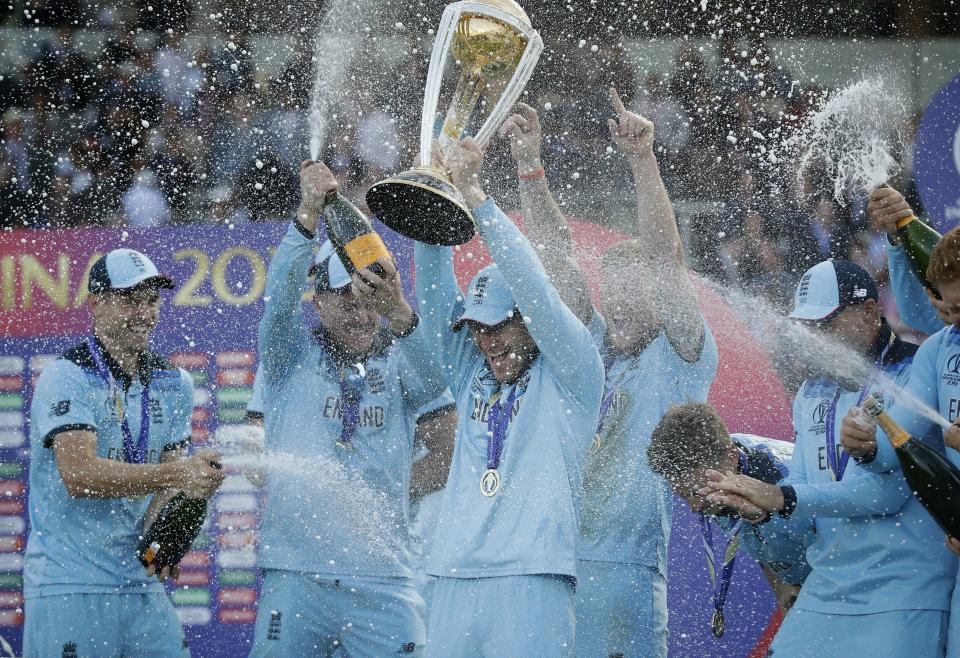 England's captain Eoin Morgan is sprayed with champagne as he raises the trophy (AP Photo/Matt Dunham)