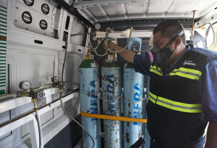 Health worker Jose Antonio Peña refills oxygen tanks for patients with COVID-19 in the Iztapalapa district of Mexico City, Tuesday, Jan. 26, 2021. The city is offering free oxygen refills for patients with COVID-19. (AP Photo/Marco Ugarte)