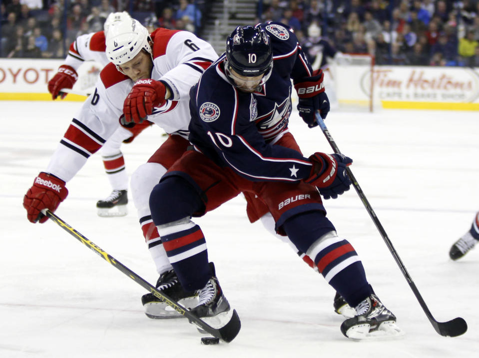 Carolina Hurricanes' Tim Gleason, left, reaches for the puck against Columbus Blue Jackets' Jack Skille during the second period of an NHL hockey game in Columbus, Ohio, Tuesday, Nov. 4, 2014. (AP Photo/Paul Vernon)