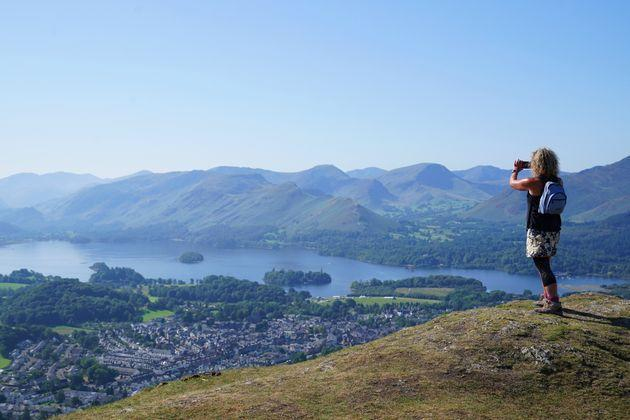 <strong>A walker takes in the view of Derwent Water in Cumbria.</strong> (Photo: Owen HumphreysPA)