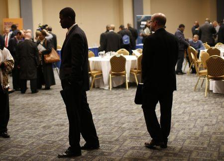 Job seekers stand in a room of prospective employers at a career fair in New York City