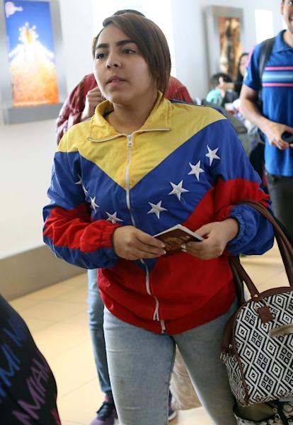 A Venezuelan migrant waits to board her flight at Lima's international airport, one of a group of about 100 who took up an a government offer to fly home after experiencing difficulties in Peru, on August 27, 2018