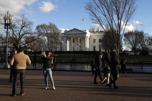 Tourists stand on Pennsylvania Avenue by the White House at sunset, Friday March 22, 2019, in Washington, after the news that special counsel Robert Mueller has concluded his investigation into Russian election interference and possible coordination with associates of President Donald Trump and delivered his final report to Attorney General William Barr. (AP Photo/Jacquelyn Martin)
