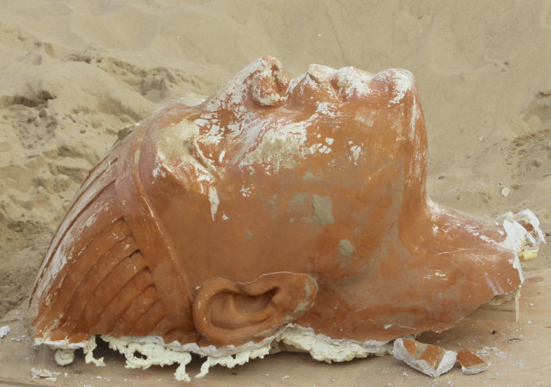 """In this Nov. 3, 2017 photo provided by the Guadalupe-Nipomo Dunes Center is a gigantic deep terra-cotta-colored head that was found recently during an excavation of the buried movie set from the 1923 Cecil B. DeMille epic film """"The Ten Commandments,"""" in Guadalupe, Calif. The 300-pound sphinx is the second recovered from the Guadalupe-Nipomo Dunes. After the filming DeMille ordered everything buried in the dunes 175 miles northwest of Los Angeles. (Guadalupe-Nipomo Dunes Center via AP)"""