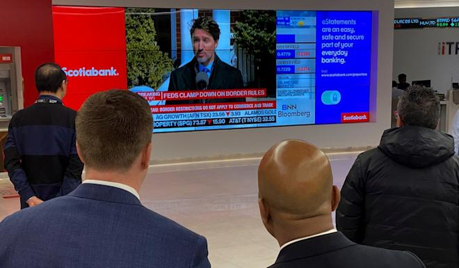 At a bank in Toronto on Monday, people watch Canadian Prime Minister Justin Trudeau's announcement of measures to combat the spread of coronavirus. Photo: Reuters