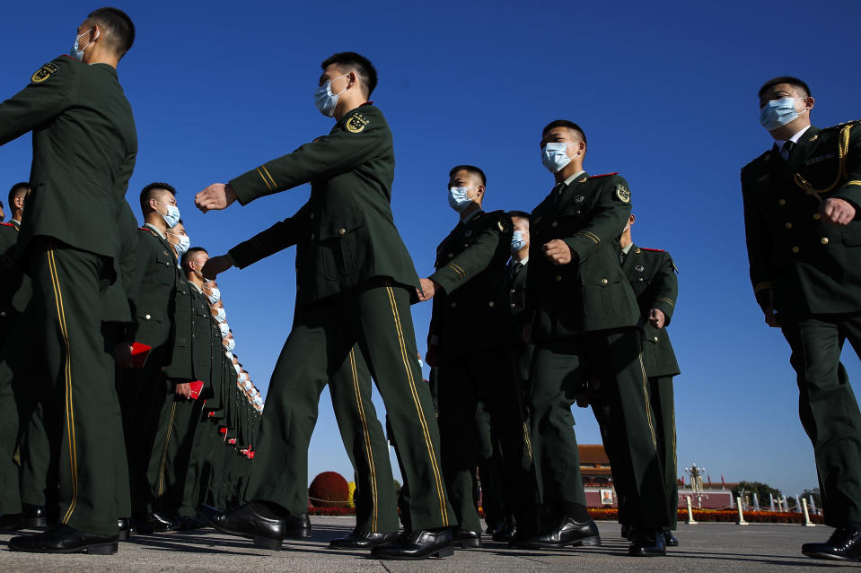 Chinese paramilitary policemen wearing face masks to help curb the spread of the coronavirus march to the Great Hall of the People to attend the commemorating conference on the 70th anniversary of China's entry into the 1950-53 Korean War, in Beijing Friday, Oct. 23, 2020. (AP Photo/Andy Wong)