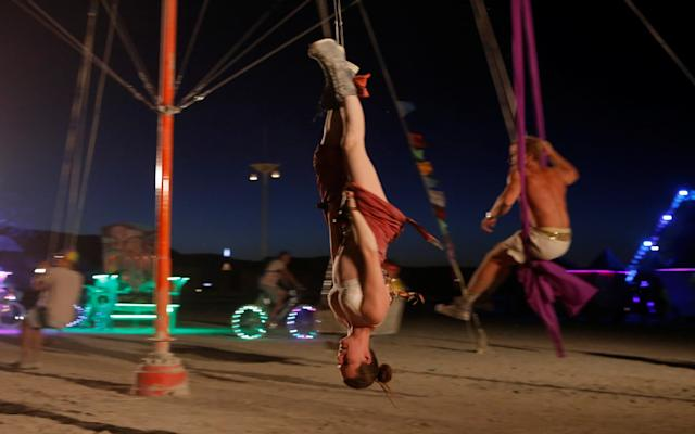 <p>A participant rides a swing as approximately 70,000 people from all over the world gathered for the annual Burning Man arts and music festival in the Black Rock Desert of Nevada, Aug. 28, 2017. (Photo: Jim Urquhart/Reuters) </p>