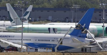 Workers on lifts are pictured near the tail of a Boeing 787-8 Dreamliner being built for for Xiamen Airlines in Everett, Washington