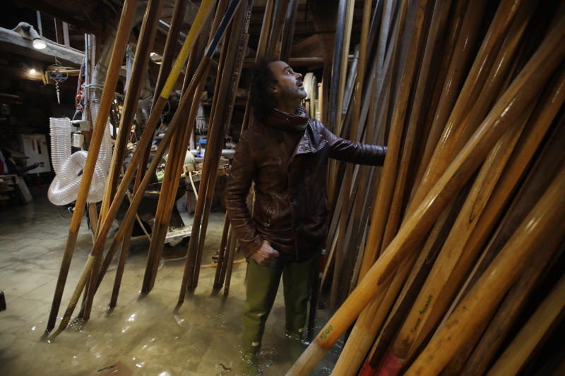 In this photo taken on Sunday, Nov. 17, 2019, Paolo Brandolisio stands in his oars flooded laboratory, in Venice, Italy. Venetians are fed up with what they see as an inadequate to the city's mounting problems: record-breaking flooding, damaging cruise ship traffic and over-tourism. They feel largely left to their own devices, and with ever fewer Venetians living in the historic part of the city to defend its interests and keep it from becoming a theme park or museum.(AP Photo/Luca Bruno)